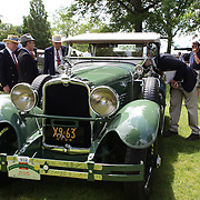 Judges make a close inspection of a 1928 Stutz BB at the Greenwich Concours d'Elegance Festival of Speed and Style featuring great classic vintage cars. Roger Sherman Baldwin Park, Greenwich, Connecticut, USA.  2nd June 2012. Photo Tim Clayton