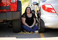 """Amber Makham sits in the shade between two cars in line for casting for season 11 of """"The Biggest Loser"""" television show in Broomfield, Colorado July 17, 2010.  Over 600 people waited in sweltering heat for a chance to be on the show and win $250,000.   REUTERS/Rick Wilking (UNITED STATES)"""