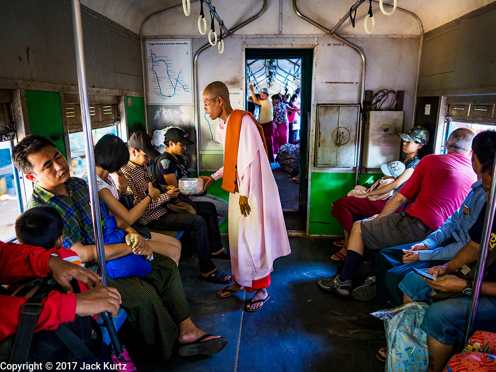 25 NOVEMBER 2017 - YANGON, MYANMAR: A bhikkhuni (Buddhist nun) solicits alms on the Yangon Circular Train. The Yangon Circular Train is a 45.9-kilometre (28.5 mi) 39-station two track loop system connects satellite towns and suburban areas to downtown. The train was built during the British colonial period, the second track was built in 1954. Trains currently run both directions (clockwise and counter-clockwise) around the city. The trains are the least expensive way to get across Yangon and they are very popular with Yangon's working class. About 100,000 people ride the train every day. A a ticket costs 200 Kyat (about .17¢ US) for the entire 28.5 mile loop.    PHOTO BY JACK KURTZ