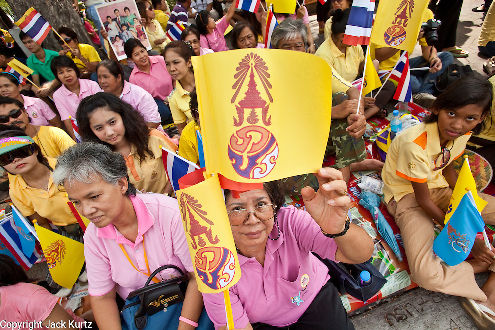 05 MAY 2010 - BANGKOK, THAILAND: A woman holds up the royal flag while she and others wait for Thai King Bhumibol Adulyade, in front of the Grand Palace in Bangkok, Wednesday, May 5. Wednesday was Coronation Day in Thailand, marking the 60th anniversary of the coronation of Thai King Bhumibol Adulyade, also known as Rama IX. He is the world's longest serving current head of state and the longest reigning monarch in Thai history. He has reigned since June 9, 1946 and his coronation was on May 5, 1950, after he finished his studies. The King is revered by the Thai people. Thousands lined the streets around the Grand Palace hoping to catch a glimpse of the King as his motorcade pulled into the palace. The King has been hospitalized since September 2009, making only infrequent trips out of the hospital for official functions, like today's ceremonies.   PHOTO BY JACK KURTZ