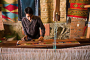 Gaspar Bautista Chavez weaves a wool carpet on a mechanical loom in his family's workshop in Teotitlan del Valle, Oaxaca state, Mexico on July 28, 2008. The Zapotec town is famous for carpet weaving, the better artists producing very high quality work using natural dyes and drawing from both traditional and contemporary designs.