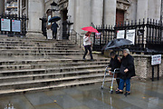 An elderly lady using a Zimmer frame endures heavy rainfall on an autumn afternoon outside St. Martin-in-the-Fields church on Trafalgar Square, on 24th October 2019, in Westminster, London, England.