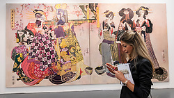 "© Licensed to London News Pictures. 19/05/2016. London, UK. A woman stands in front of Wolfe von Lenkiewicz's ""The Flower Women"".  Art16 opens at Olympia, in west London.  Now in its fourth edition, the fair brings together over 100 galleries from more than 30 countries showcasing a diverse cross-section of work by contemporary artists from around the world for buyers and art enthusiasts to visit. Photo credit : Stephen Chung/LNP"