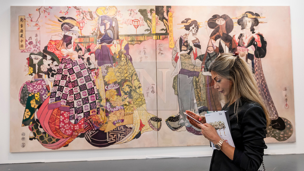 """© Licensed to London News Pictures. 19/05/2016. London, UK. A woman stands in front of Wolfe von Lenkiewicz's """"The Flower Women"""".  Art16 opens at Olympia, in west London.  Now in its fourth edition, the fair brings together over 100 galleries from more than 30 countries showcasing a diverse cross-section of work by contemporary artists from around the world for buyers and art enthusiasts to visit. Photo credit : Stephen Chung/LNP"""