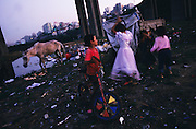 Children playing underneath the motorway, the city's outskirts in view from their tents. . Their families earn their living recycling rubbish. On the periphery of Istanbul, Turkey 2006