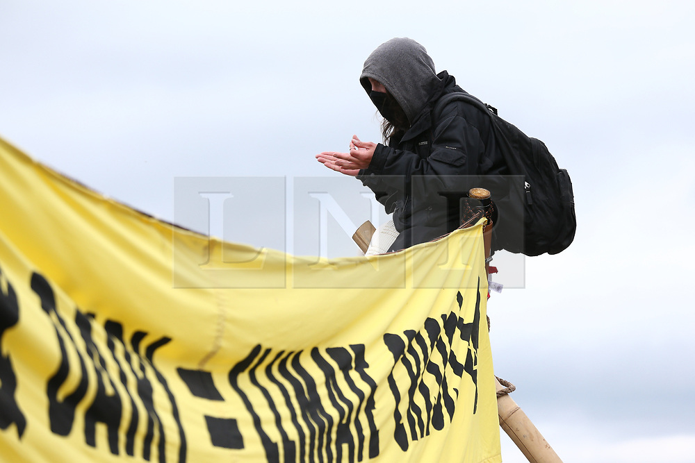 © Licensed to London News Pictures. 22/05/2021. Oldham, UK. An Animal Rebellion activist sits atop a pole at the Heywood Distribution Park in Oldham, which supplies hundreds of McDonald's restaurants in the region. The animal rights group are demanding that McDonald's commit to a fully plant-based operation by 2025. Photo credit: Adam Vaughan/LNP