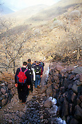 School students explore village path on trek in Atlas Mountains, Morocco