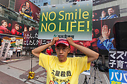 """A man wearing a Donald Trump election hat holds a sign saying, """"No Smile, No life"""" at a  small demonstration against government and societal measures to combat the COVID19 pandemic in Hachiko Square, Shibuya, Tokyo, Japan. Saturday June 12th 2021. Supporters of Masayuki Hiratsuka of the Popular Sovereignty Party of Japan, who unsuccessfully ran for Tokyo Governor in 2020, held a music festival in the iconic Hachiko Square calling the Coronavirus pandemic a lie."""