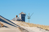 The Old Harbor Life-Saving Station, originally in Chatham, was moved to Provincetown on a barge to be included in the Cape Cod National Seashore.  While still on the barge, a winter storm obliterated the beach where the station had been. had