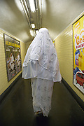 Arabic woman in white dress seen from behind when walking through a underground corridor towards subway in Paris
