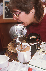 Woman with disability using mouth to hold teapot and pour cup of tea,