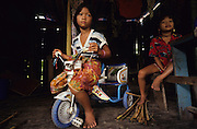 1989: Penan girls with tricycle in sulap settlement. Belaga district, Sarawak. Borneo<br /> <br /> Tropical rainforest and one of the world's richest, oldest eco-systems, flora and fauna, under threat from development, logging and deforestation. Home to indigenous Dayak native tribal peoples, farming by slash and burn cultivation, fishing and hunting wild boar. Home to the Penan, traditional nomadic hunter-gatherers, of whom only one thousand survive, eating roots, and hunting wild animals with blowpipes. Animists, Christians, they still practice traditional medicine from herbs and plants. Native people have mounted protests and blockades against logging concessions, many have been arrested and imprisoned.