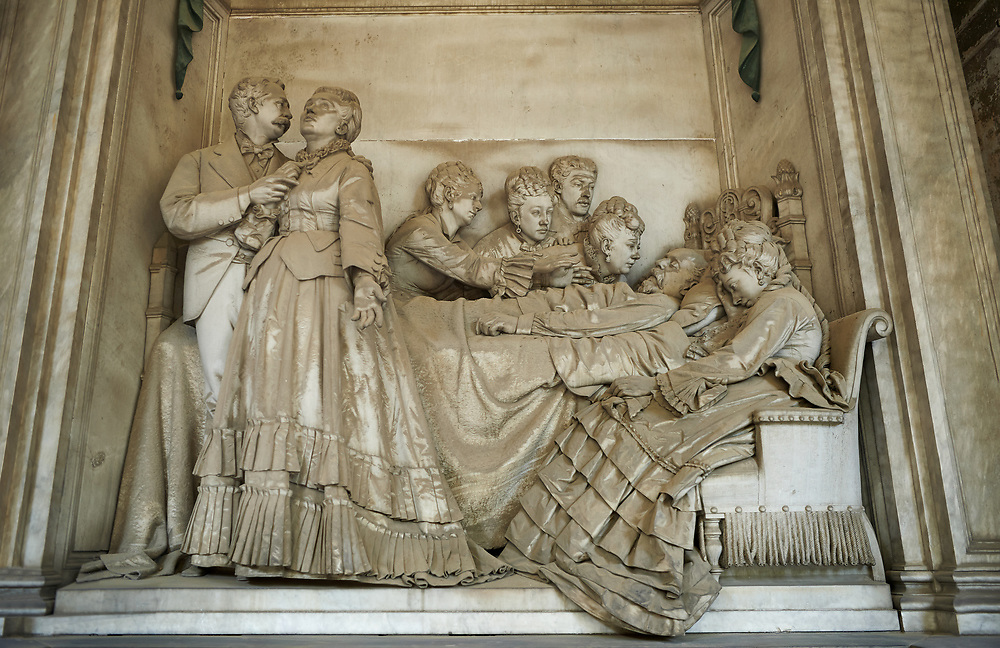 Picture and image of the stone sculpture of a grieving family arounf the death bed of an old man sculpted in Borgeoise Realistic style by A Rivalta in 1872.  The Raggio family tomb, Scection D no 10, the monumental tombs of the Staglieno Monumental Cemetery, Genoa, Italy .<br /> <br /> Visit our ITALY PHOTO COLLECTION for more   photos of Italy to download or buy as prints https://funkystock.photoshelter.com/gallery-collection/2b-Pictures-Images-of-Italy-Photos-of-Italian-Historic-Landmark-Sites/C0000qxA2zGFjd_k<br /> If you prefer to buy from our ALAMY PHOTO LIBRARY  Collection visit : https://www.alamy.com/portfolio/paul-williams-funkystock/camposanto-di-staglieno-cemetery-genoa.html