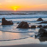 The sun sets over rocks at Panther Beach, north of Santa Cruz, California.