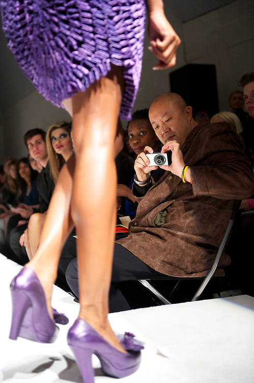 A front row seated guest photographs a model on the catwalk during  the Pierre Garroudi autumn 2011 collection at his gallery in London on 19 February 2011.