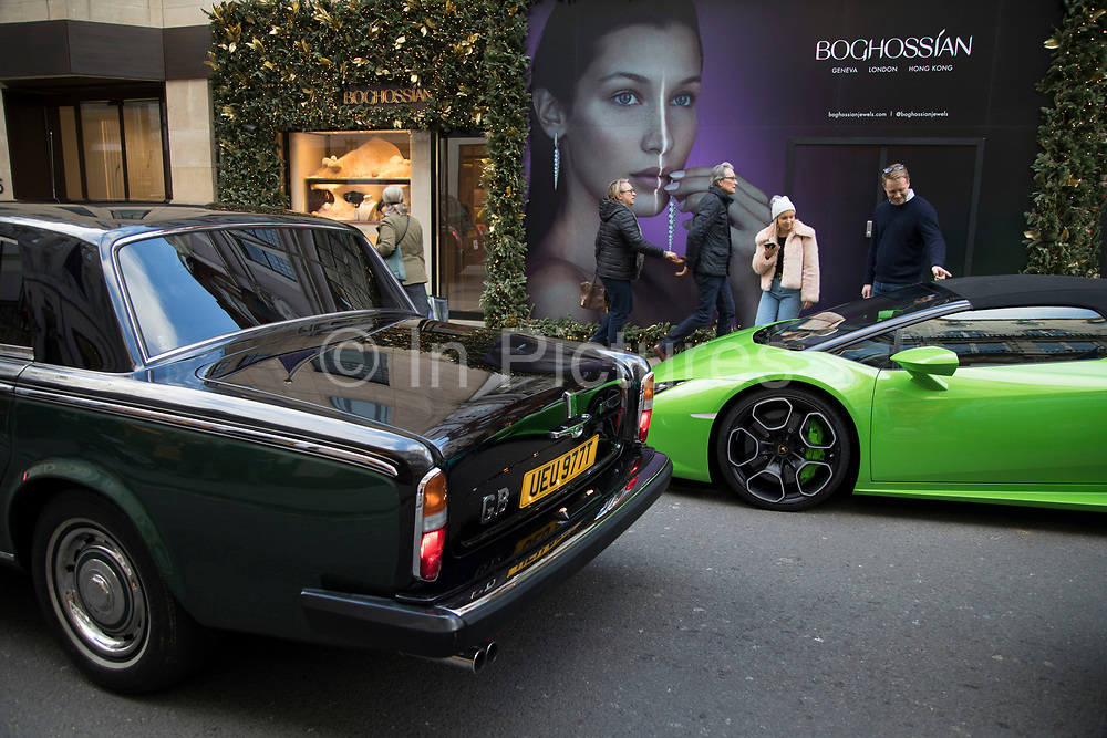Lamborghini supercar is passed by a vintage predecessor Rolls Royce on Bond Street in London, England, United Kingdom. Cars like this are often seen parked on this exclusive shopping street for the super wealthy. This is one of the principal streets in the West End shopping district and is more upmarket. It has been a fashionable shopping street since the 18th century. Technically Bond Street does not exist: The southern section is known as Old Bond Street, and the northern section, which is rather more than half the total length, is known as New Bond Street. The rich and wealthy shop here mostly for high end fashion.