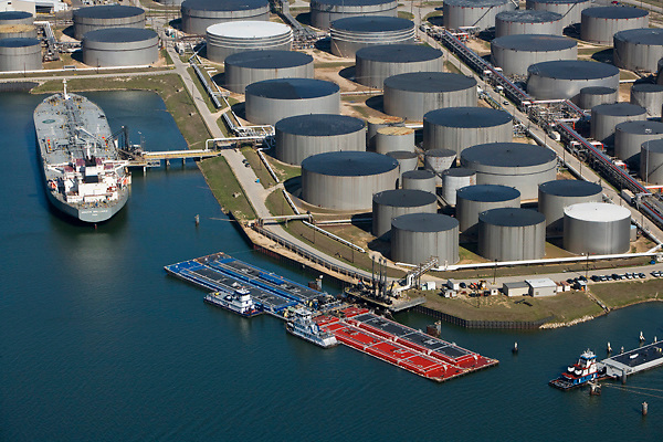 Aerial view of oil tanker and barges moored by a tank farm in the Port of Houston.
