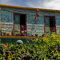 South America, Argentina, Buenos Aires. Colorfully painted buidling and balcony overlooking La Boca street.