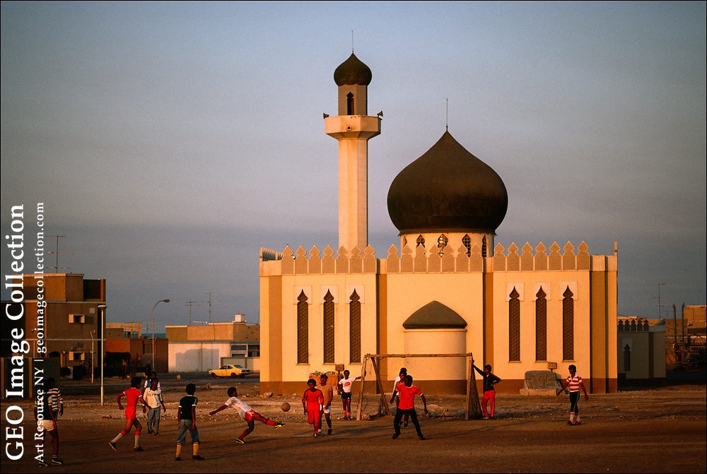 Young men play soccer in front of a Shiite, or Shia, mosque in Isa Town --in Arabic مدينة عيسى--middle class enclave on the Persian Gulf island of Bahrain. The name Isa refers to Isa ibn Salman Al-Khalifah, the late ruler of Bahrain from 1961 to 1999.