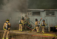 In-training firefighters from Gilford Fire department enter the Phelps Barn during controlled burn exercises at Gunstock Saturday.  (Karen Bobotas Photo/for The Laconia Daily Sun)