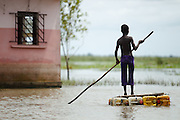 A boy uses a makeshift raft to move around in the town of Sahouicomey, Benin on Sunday October 24, 2010. The village, which is normally subject to seasonal flooding, has been severely hit by exceptional increases in water levels that have destroyed many houses and killed five people. Children will use such rafts to go to class when the school reopens in about a week.