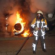 Autobrand Gemeenlandslaan Huizen, auto op de kop, brandweer blussen, vernieling