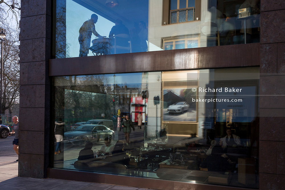 With a Porsche luxury car ad reflected in the window, a restaurant waiter attends to a corner table's customers, on 20th January 2020, in London, England.