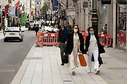 Shoppers wearing face masks on Bond Street on 25th May 2021 in London, United Kingdom. These high end brands are seen next to each other on a very ordinary wall. Bond Street is one of the principal streets in the West End shopping district and is very upmarket. It has been a fashionable shopping street since the 18th century. The rich and wealthy shop here mostly for high end fashion and jewellery.
