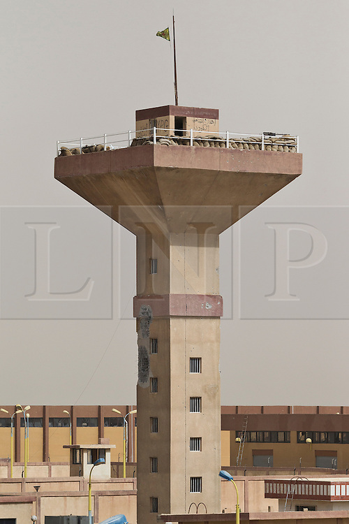 © Licensed to London News Pictures. 28/09/2014. Al-Yarubiyah, Syria. A tower, used as an observation post by Syrian-Kurdish YPG forces, shows damage caused by Islamic State tanks, Al-Yarubiyah, Syria.<br /> <br /> Facing each other across the Iraq-Syria border, the towns of Al-Yarubiyah, Syria, and Rabia, Iraq, were taken by Islamic State insurgents in August 2014. Since then The town of Al-Yarubiyah and parts of Rabia have been re-taken by fighters from the Syrian Kurdish YPG. At present the situation in the towns is static, but with large exchanges of sniper and heavy machine gun fire as well as mortars and rocket propelled grenades, recently occasional close quarter fighting has taken place as either side tests the defences of the other. Photo credit: Matt Cetti-Roberts/LNP