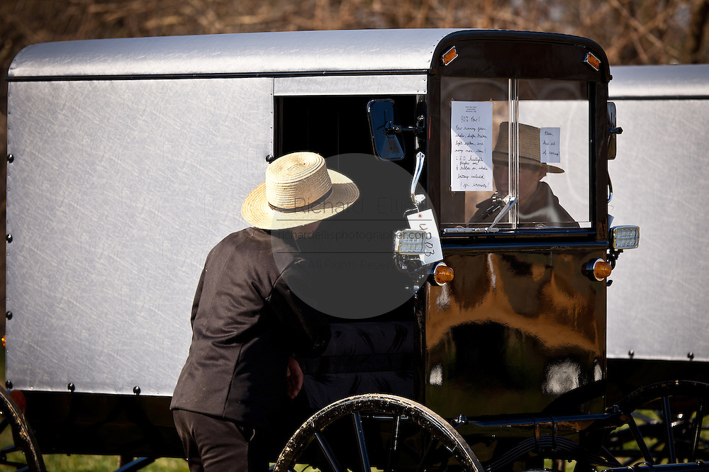 Amish men inspect a horse buggy during the Annual Mud Sale to support the Fire Department  in Gordonville, PA.