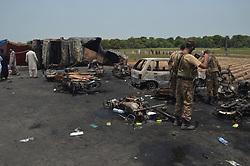 June 25, 2017 - Bawahalpur, Pakistan - Pakistani soldiers examine the oil tanker accident site in eastern Pakistan's Bawahalpur. Villagers had gathered, reportedly to collect fuel leaking from the crashed tanker, when it caught fire killing at least 140 people and 120 others injured,  in the Pakistan's eastern Punjab province. (Credit Image: © Stringer/Xinhua via ZUMA Wire)