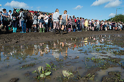 © Licensed to London News Pictures. 28/08/2015. Reading Festival, UK. Festival goers at Reading Festival on Day 1 of the festival walking through pools of mud in wellington boots.  The arena gates are due to open for the first time a few minutes later and queues of festival goers are waiting to enterPhoto credit: Richard Isaac/LNP