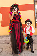A mother in Catrina costume talks on her mobile phone as her son in costume waits during celebrations for the Day of the Dead festival known in Spanish as Día de Muertos at the town square October 31, 2013 in Oaxaca, Mexico.  The festival celebrates the lives of those that died.