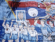 communist Propaganda, Vientiane, Laos, Asia. A flag of Laos and a Flag of URSS are on top of the decay paint. Workers and studients raise the fist in glory to the country.