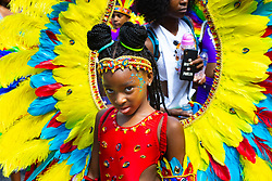 A girl shyly glances at the camera as day one, Children's Day, of the Notting Hill Carnival gets underway in London. London, August 25 2019.