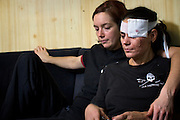 """Molly Kendall, left, comforts crewmate Zin Rain after she was injured by a hard fall when large swells rolled Sea Shepherd's ship, the M/Y Steve Irwin, on Friday, Dec. 16, 2009 in the Southern Ocean.  Some of the greater dangers on campaign come not from clashes with the whaling fleet, but from the simple realities of being at sea. """"Damn it, I just dreamed last night that I was wearing an eye patch!"""", said Rain. (Photo by Adam Lau)"""