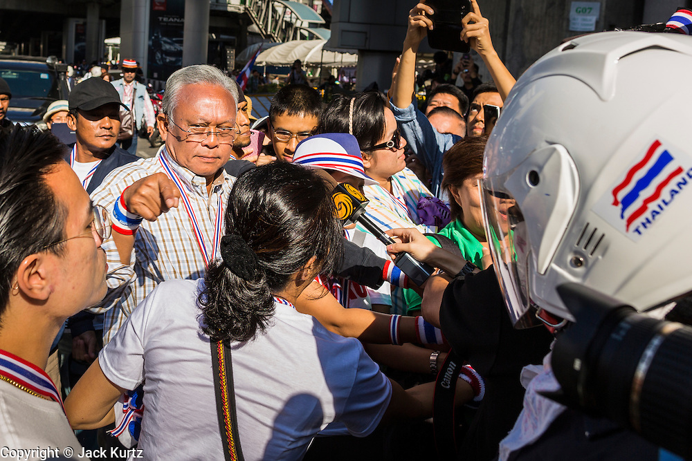 """15 JANUARY 2014 - BANGKOK, THAILAND: SUTHEP THAUGSUBAN, former Deputy Prime Minister of Thailand and leader of the Shutdown Bangkok anti-government protests, arrives at the protest site in the Asoke intersection. Tens of thousands of Thai anti-government protestors continued to block the streets of Bangkok Wednesday to shut down the Thai capitol. The protest, """"Shutdown Bangkok,"""" is expected to last at least a week. Shutdown Bangkok is organized by People's Democratic Reform Committee (PRDC). It's a continuation of protests that started in early November. There have been shootings almost every night at different protests sites around Bangkok. The malls in Bangkok are still open but many other businesses are closed and mass transit is swamped with both protestors and people who had to use mass transit because the roads were blocked.    PHOTO BY JACK KURTZ"""
