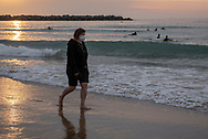 A girl, wearing a protective face mask, walks on the beach at sunset. Donostia (Basque Country). May 7, 2020. Some outdoor activities have been allowed as Spain is going through the plan of downscaling following an ongoing plan to leave the confinement ordered by the Spanish government to prevent the spread of the COVID-19. (Gari Garaialde / Bostok Photo)