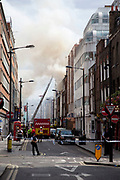 A fire broke out on Dean Streen in Soho, Central London on Friday afternoon. The fire, in a five storey building in the heart of the city raged with firefighters struggling to get the blaze under control. In the nearby streets workers finishing early stood in the smoke filled streets having an end-of-the-week beer in the ghostly atmosphere.
