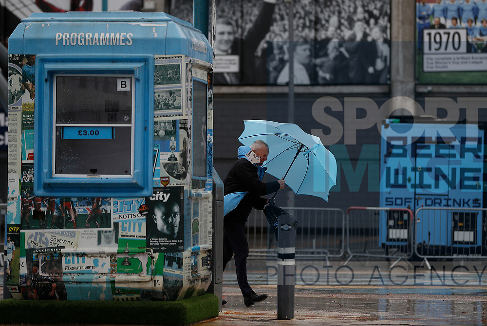 A man struggles with his umbrella after the Premier League match between Manchester City and West Ham United was postponed because of weather conditions at the Etihad Stadium, Manchester. Picture date: 9th February 2020. Picture credit should read: Darren Staples/Sportimage