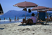 Sandy beach children playing in the sea and people sitting under sunshades, Les Sablettes, French Riviera, France 1974