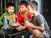 11 JANUARY 2015 - BANGKOK, THAILAND: Boys watch videos on a tablet computer in Pak Khlong Talat, the flower market in Bangkok. The market, which runs along the Chao Phraya River, is the largest flower market in Thailand.     PHOTO BY JACK KURTZ