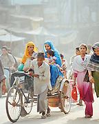 Man pushing rickshaw in a busy street, Lucknow, Uttar Pradesh, India