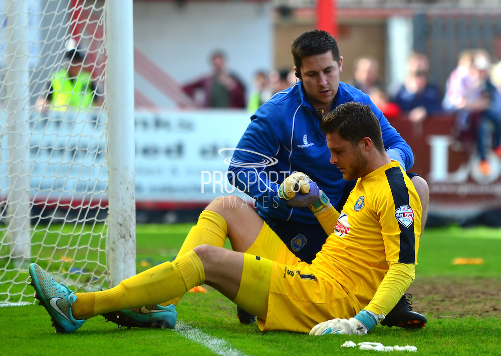 Jayson Leutwiler being treated by physio during the Sky Bet League 2 match between Cheltenham Town and Shrewsbury Town at Whaddon Road, Cheltenham, England on 25 April 2015. Photo by Alan Franklin.