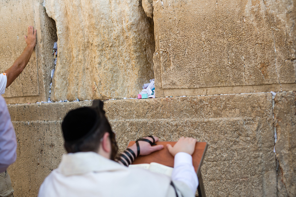 Notes containing prayers and messages which were left by visitors in the cracks between the stones of the Western Wall are seen as Jewish men pray at Judaism's holiest prayer site, in the Old City of Jerusalem, Israel, on September 17, 2017. The clean-up which takes place ahead of the upcoming Jewish New Year Holiday, clears the wall's crevices and frees up space for more notes that people of all faiths slip between its stones, believing that requests deposited at the site are more likely to be heard by God.