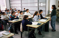 Secondary school classroom in Barcelona with teacher standing at front of class and pupils sitting at desks,
