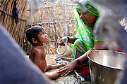 Meenakshi, 7, a child born with mental and physical disabilities from a gas-affected mother, is being washed by Sorom Bai, 35, in their home in the impoverished Oriya Basti Colony, in Bhopal, Madhya Pradesh, India, near the abandoned Union Carbide (now DOW Chemical) industrial complex.