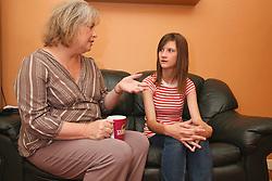 Woman and teenage girl talking on sofa.