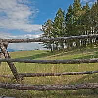 A jack-leg fence stands beside pastures in the southern Bridger Mountains. the Absaroka Mountains rise in the background.