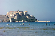 Calvi, Corsica, France in late 1950s people swimming with town citadel in background